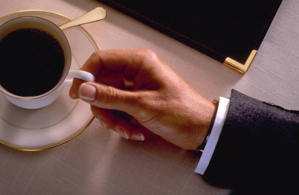 Ruka muže s šálkem kávy